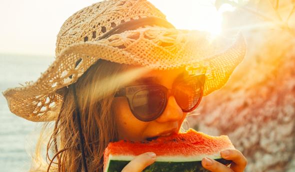 BBGR, femme avec un chapeau, portant des lunettes équipées de verres solaire et mangeant une part de pastèque, en été.